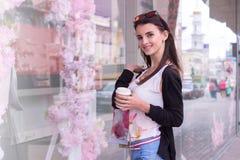 A morena nova bonita olha a câmera e guardar uma xícara de café Fotografia de Stock