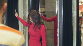 Morena nova bonita que mostra o vestido vermelho a seu noivo no vestuario video estoque