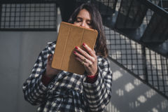 Morena nova bonita usando sua tabuleta nas ruas da cidade Imagens de Stock