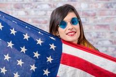 Morena nova com óculos de sol azuis e a bandeira americana Foto de Stock