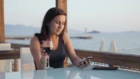 Morena nova com vidro do vinho tinto usando seu Smartphone ao sentar-se no café pelo mar no por do sol Imagens de Stock Royalty Free