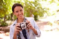 Morena nova de sorriso com câmera velha Fotos de Stock Royalty Free