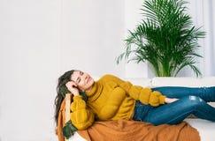 Morena nova feliz nas calças de brim e na camiseta que sonham no sofá fotografia de stock