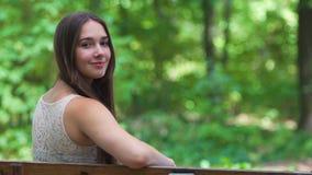 A morena nova gerencie em torno do assento no banco que sorri, mulher sente o ar livre feliz vídeos de arquivo