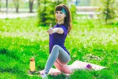 Morena nova na camisa de esportes azul na esteira da aptidão que faz exercícios fora Mulher que mostra o polegar acima imagens de stock