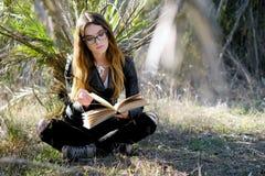 Morena nova que lê um livro fora Fotos de Stock