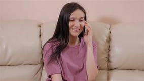 A morena nova senta-se no sofá de couro em casa e falando no telefone vídeos de arquivo