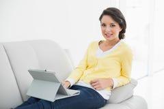 Morena ocasional de sorriso no casaco de lã amarelo usando um PC da tabuleta foto de stock
