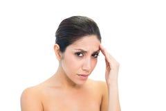 Morena olhando de sobrancelhas franzidas com uma dor de cabeça que olha a câmera Fotos de Stock