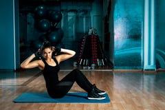 Morena que faz triturações no gym foto de stock