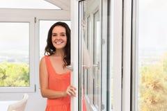 Morena que fica janelas plásticas próximas Fotos de Stock