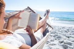 Morena que lê um livro ao relaxar na rede imagem de stock royalty free