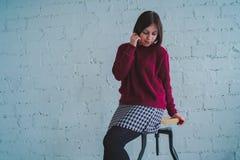 Morena que levanta com uma cadeira, contra uma parede de tijolo imagem de stock