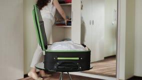 Morena que recolhe coisas em uma mala de viagem por seus feriados filme