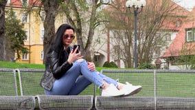 A morena senta-se em um banco da rua e escuta-se a m?sica filme