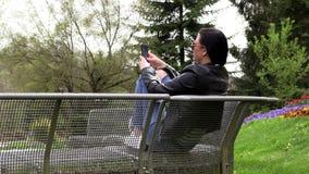 A morena senta-se em um banco da rua e escuta-se a m?sica vídeos de arquivo