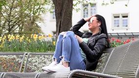 A morena senta-se em um banco da rua e escuta-se a m?sica video estoque