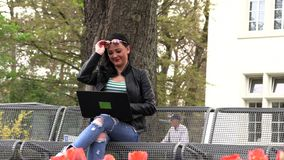 A morena senta-se em um banco da rua e trabalha-se em um computador vídeos de arquivo