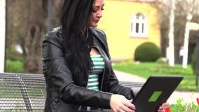 A morena senta-se em um banco da rua e trabalha-se em um computador filme