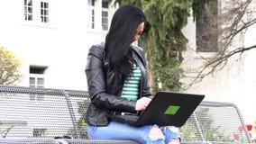 A morena senta-se em um banco da rua e trabalha-se em um computador video estoque
