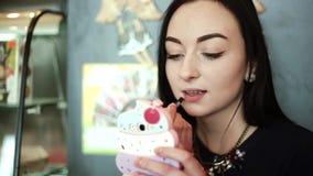 Morena 'sexy' bonita que senta-se no café, bordos colorindo com o brilho que olha no móbil como no espelho filme