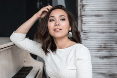 Morena 'sexy' com o cabelo muito longo que senta-se no piano fotos de stock
