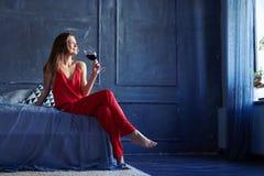 Morena sonhadora com um vidro do vinho na cama Imagem de Stock Royalty Free
