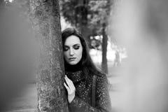 Morena surpreendente com os olhos fechados que estão a árvore próxima no parque Retrato preto e branco da mulher atrativa com Fotos de Stock Royalty Free