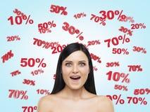 Morena surpreendida cercada por números do disconto e da venda: 10% 20% 30% 50% 70% Fotografia de Stock Royalty Free