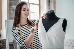 Morena talentoso que costura o vestido longo branco fotografia de stock