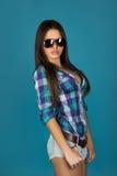 Morenita adulta encantadora en gafas de sol en fondo azul Fotografía de archivo