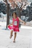 Morenita agradable de la muchacha que juega en el parque Foto de archivo