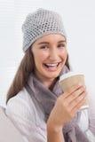 Morenita alegre con el sombrero del invierno en sostener la taza de café Foto de archivo