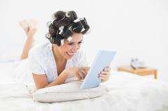 Morenita alegre en los rodillos del pelo que mienten en su cama usando su etiqueta Imagen de archivo
