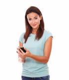 Morenita alegre que manda un SMS y que sonríe en usted Fotos de archivo libres de regalías