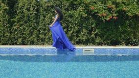 Morenita asombrosa con el cóctel en caída azul del vestido en piscina en a cámara lenta metrajes