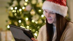 Morenita asombrosa en Santa Hat Touching que una pantalla de su tableta en la Navidad adornó a casa y sonrisa Mujer emocional almacen de metraje de vídeo