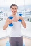 Morenita atlética alegre que ejercita con pesas de gimnasia Foto de archivo