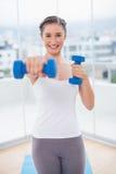 Morenita atlética sonriente que ejercita con pesas de gimnasia Foto de archivo libre de regalías