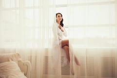 Morenita atractiva atractiva en la presentación blanca del vestido Imagen de archivo