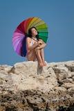 Morenita atractiva con el paraguas iridiscente en la playa rocosa salvaje Imagen de archivo libre de regalías