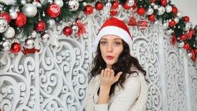 Morenita atractiva con el pelo largo que hace beso del aire y que sonríe mirando la cámara en fondo adornado la Navidad almacen de video