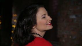 Morenita atractiva en ligar rojo del vestido, bailando y metrajes