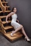 Morenita atractiva en un vestido blanco que se sienta en las escaleras de madera Fotos de archivo