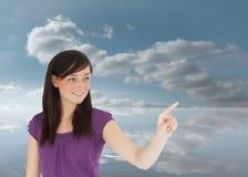 Morenita atractiva que señala algo con su finger Imagenes de archivo