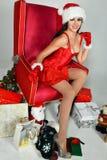 Morenita atractiva vestida como señora Papá Noel que plantea la sentada bonita en butaca clásica foto de archivo