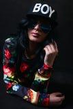 Morenita bastante atractiva en un casquillo negro y vidrios. Muchacha del Swag. Molestia Imagen de archivo