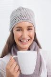 Morenita bonita alegre con el sombrero del invierno en sostener la taza de café Imagenes de archivo