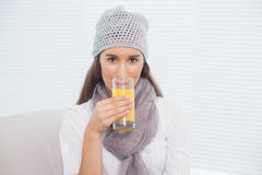 Morenita bonita con el sombrero del invierno en la consumición del zumo de naranja Foto de archivo