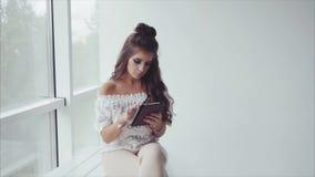 Morenita bonita de la mujer usando su tableta en el fondo blanco cerca de la ventana metrajes